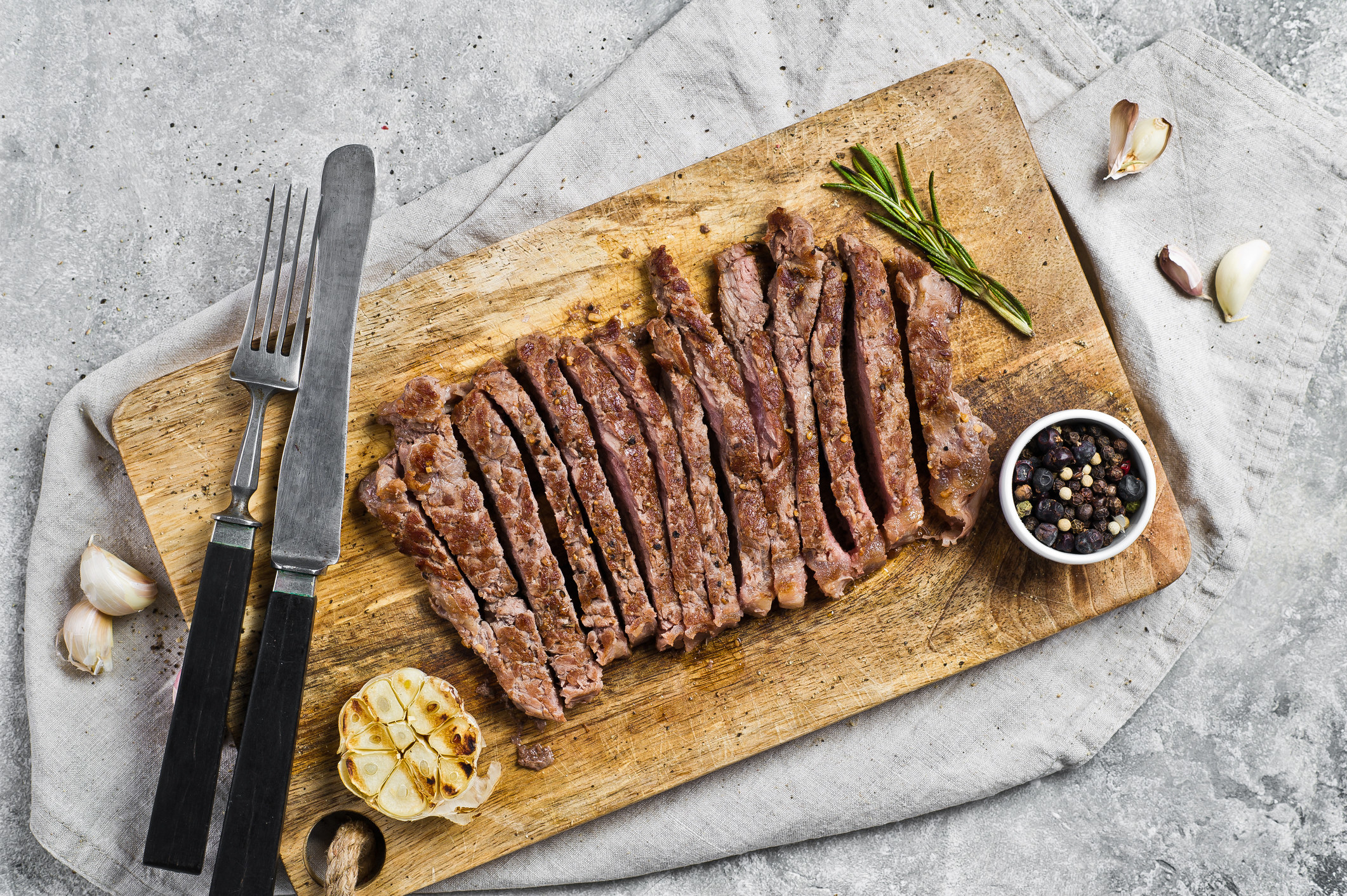 A cutting board topped with sliced steak.