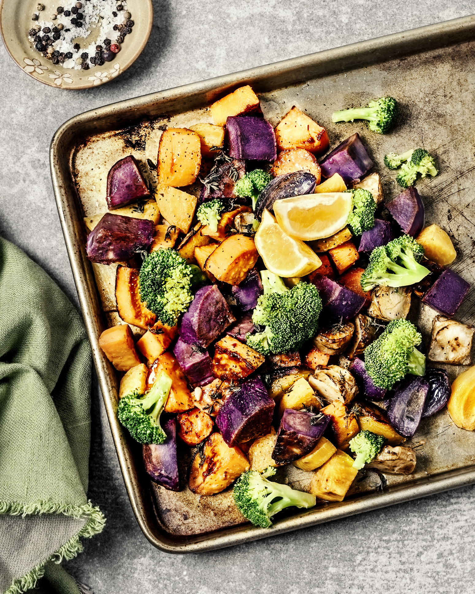 A sheet pan of different roasted veggies like broccoli and sweet potato.