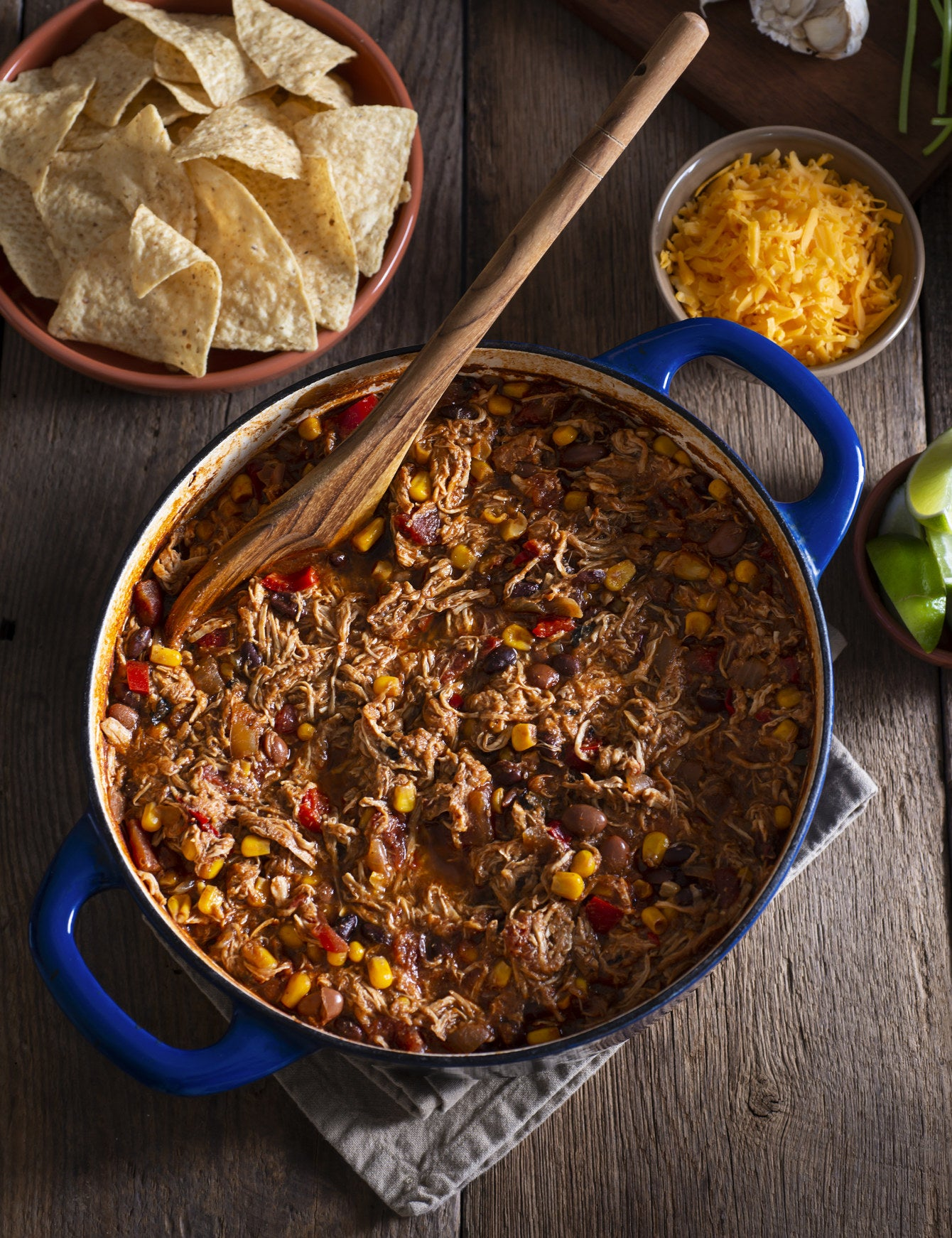 A big pot of chili with shredded chicken and cheese.