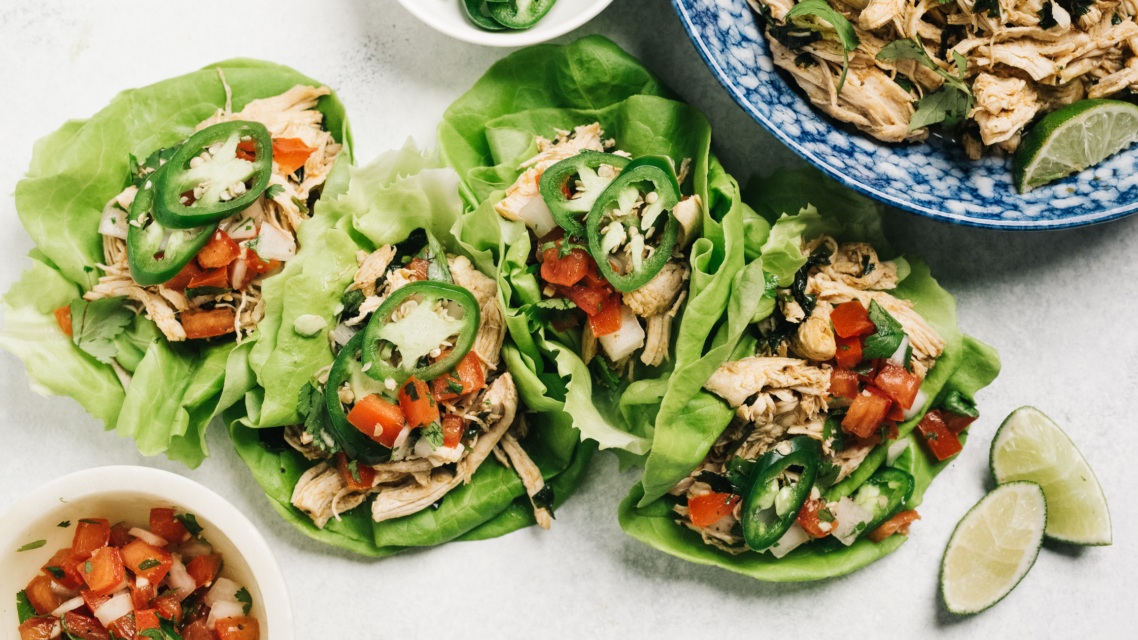 Lettuce wraps made from shredded chicken topped with veggies.