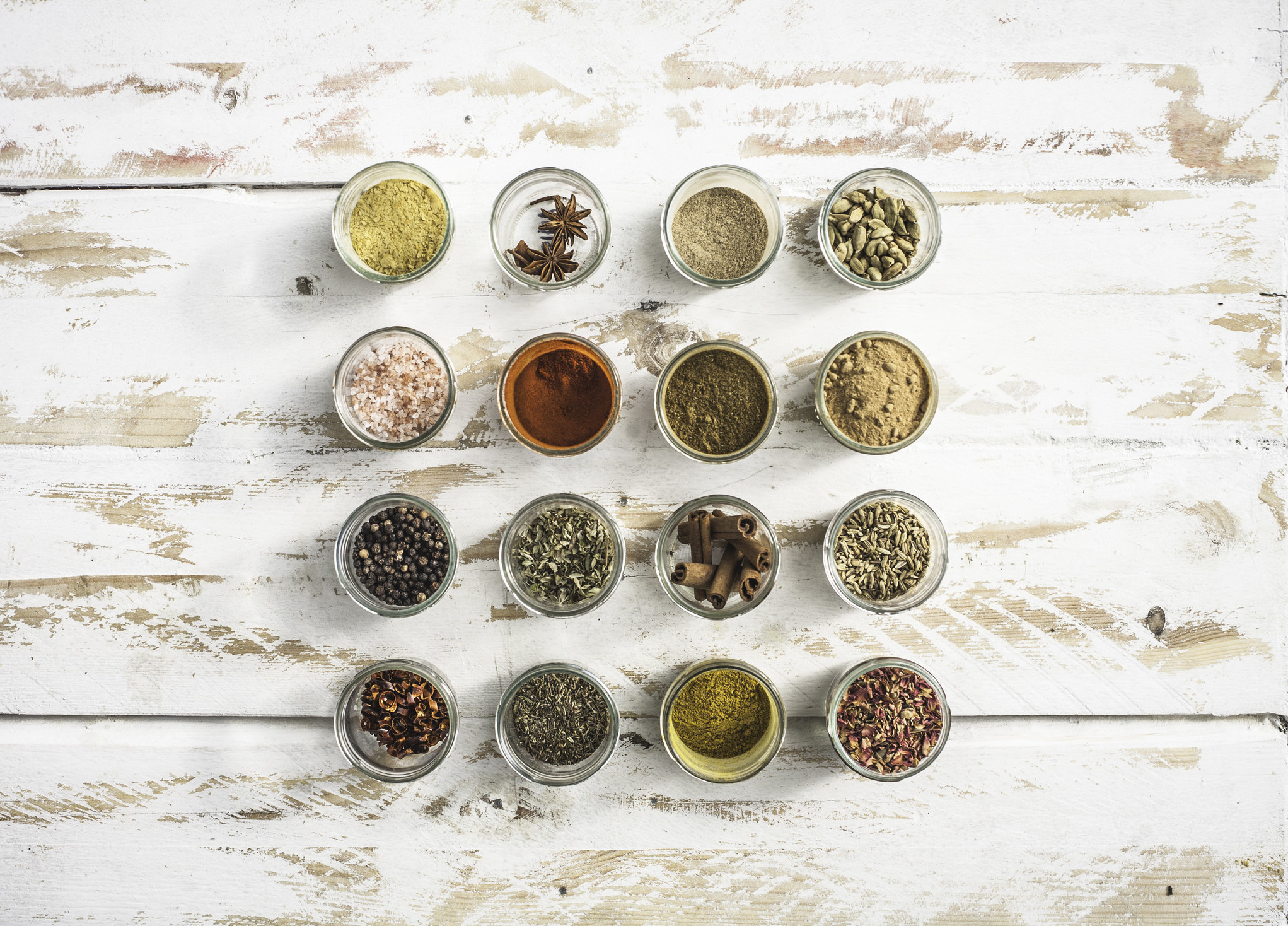Different spices in small glass bowls.
