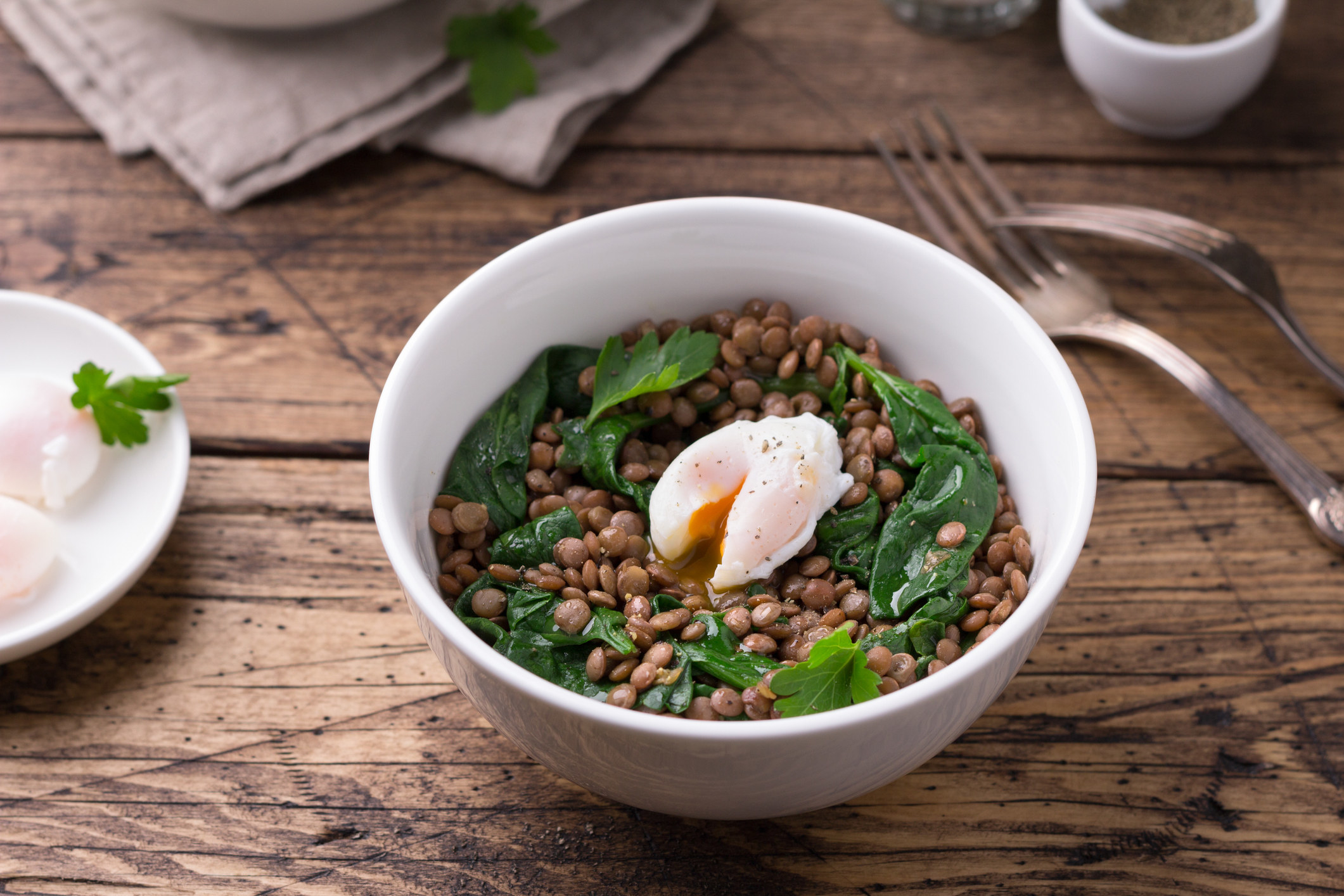 A bowl of lentils with greens and a poached egg.