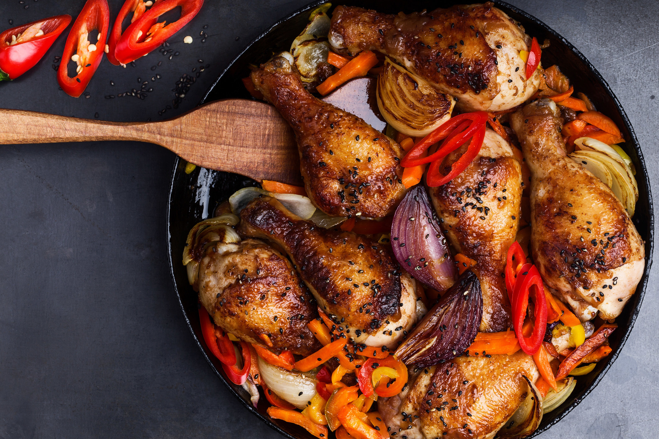 Chicken drumsticks with peppers and garlic in a cast-iron skillet.