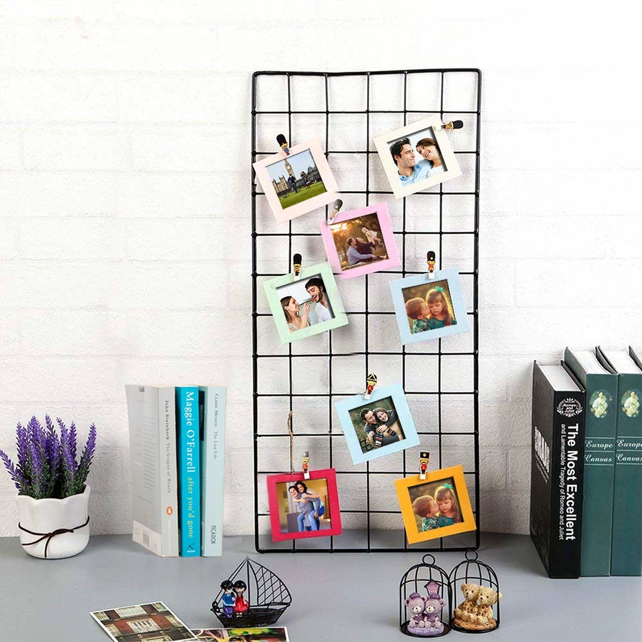 The black metal grid is kept on a work desk. It's being used to display photos.