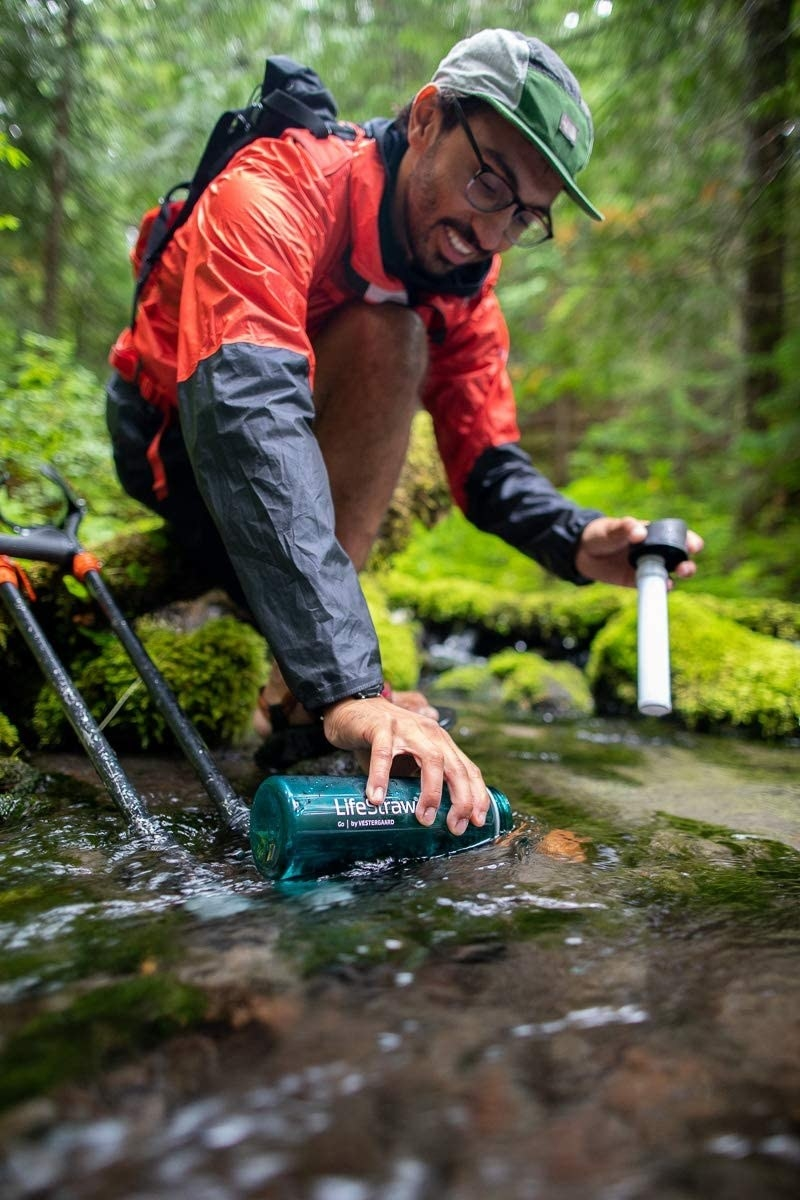 a person getting water from lake in the woods with the LifeStraw bottle