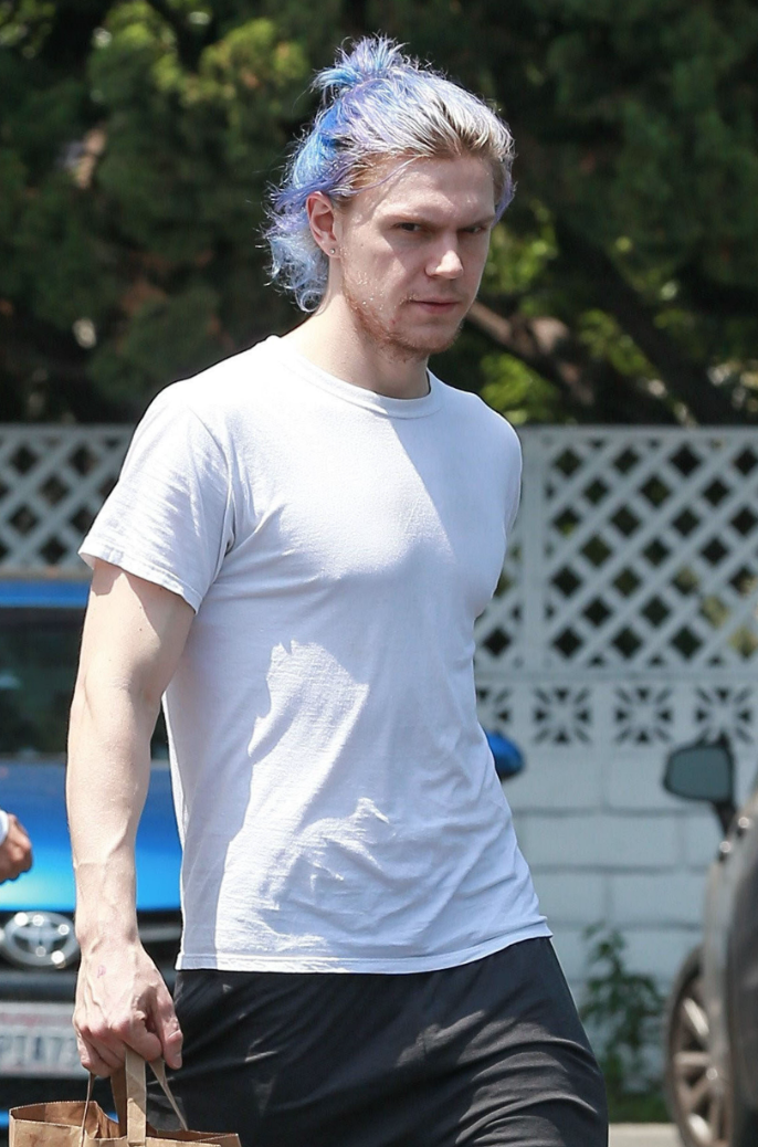 Evan Peters shows off blue hair as he walks out of a grocery store.