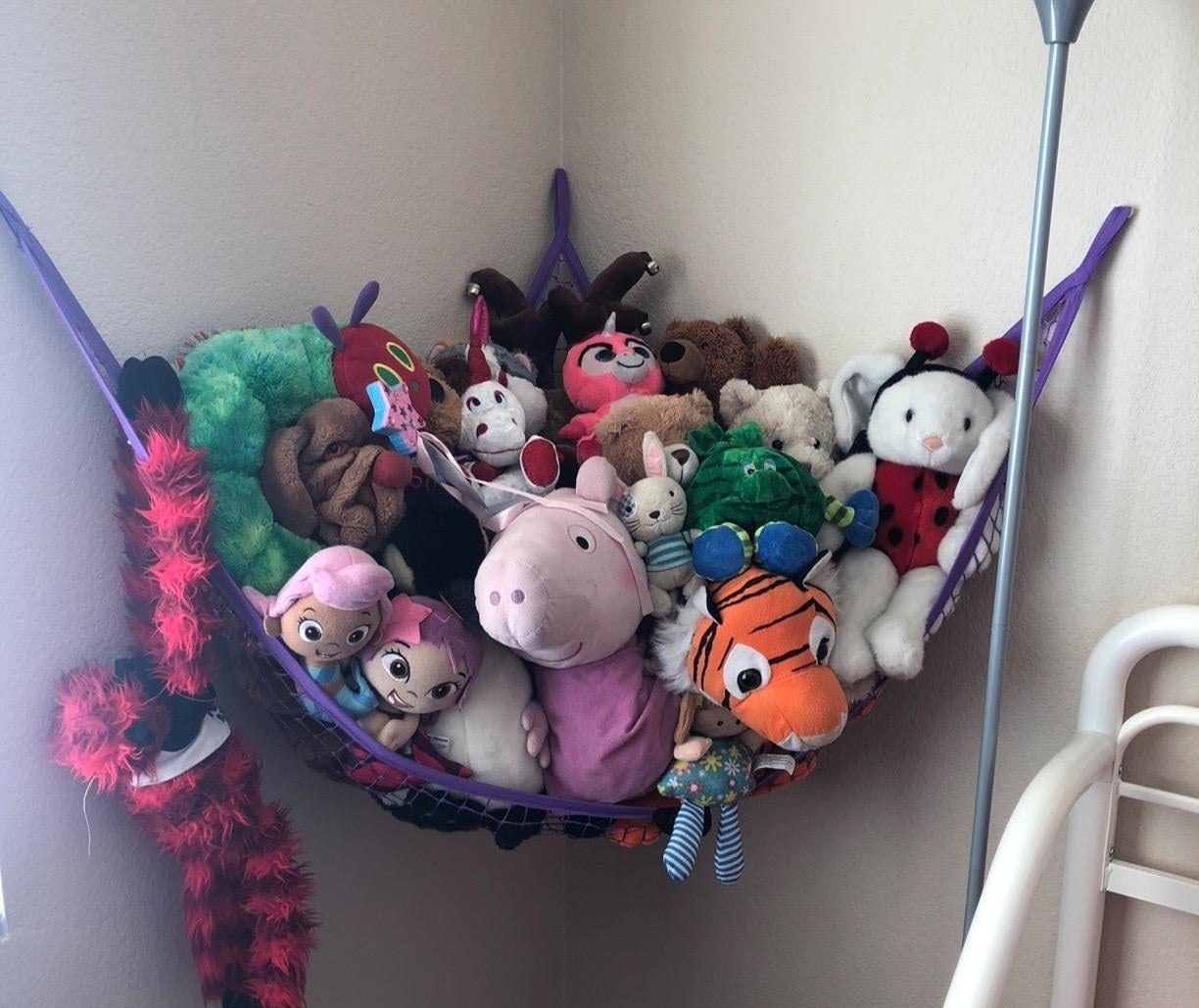 reviewer photo showing all their stuffed animals in a purple hammock