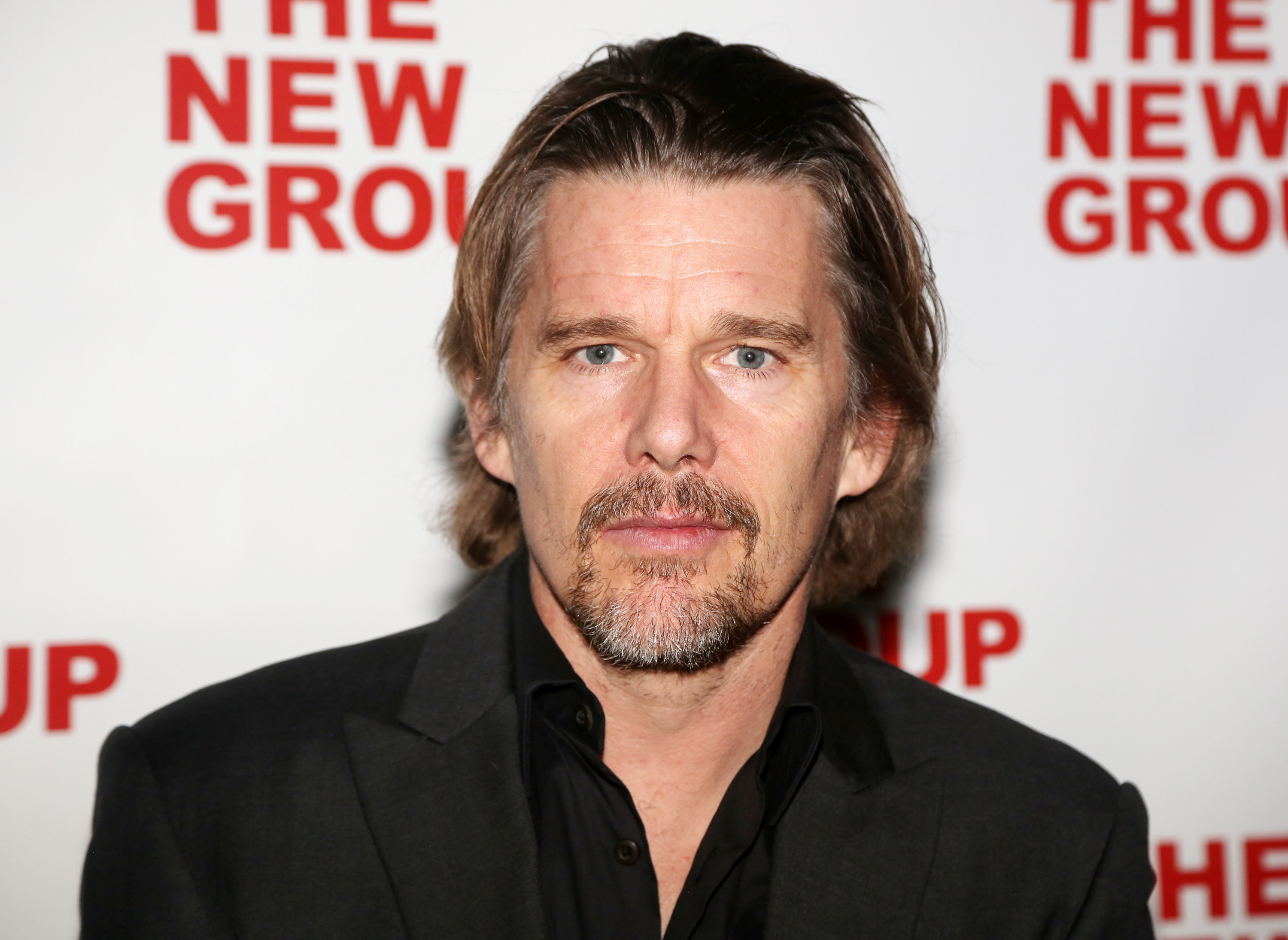 Ethan Hawke in a black shirt open at the collar