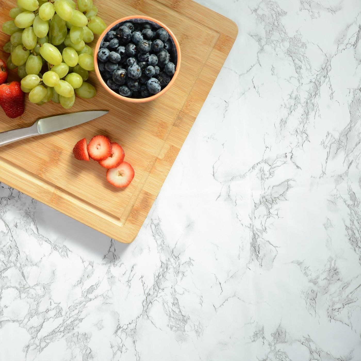 aerial view of con-tact marble adhesive on a kitchen counter on which sits a cutting board with fruit