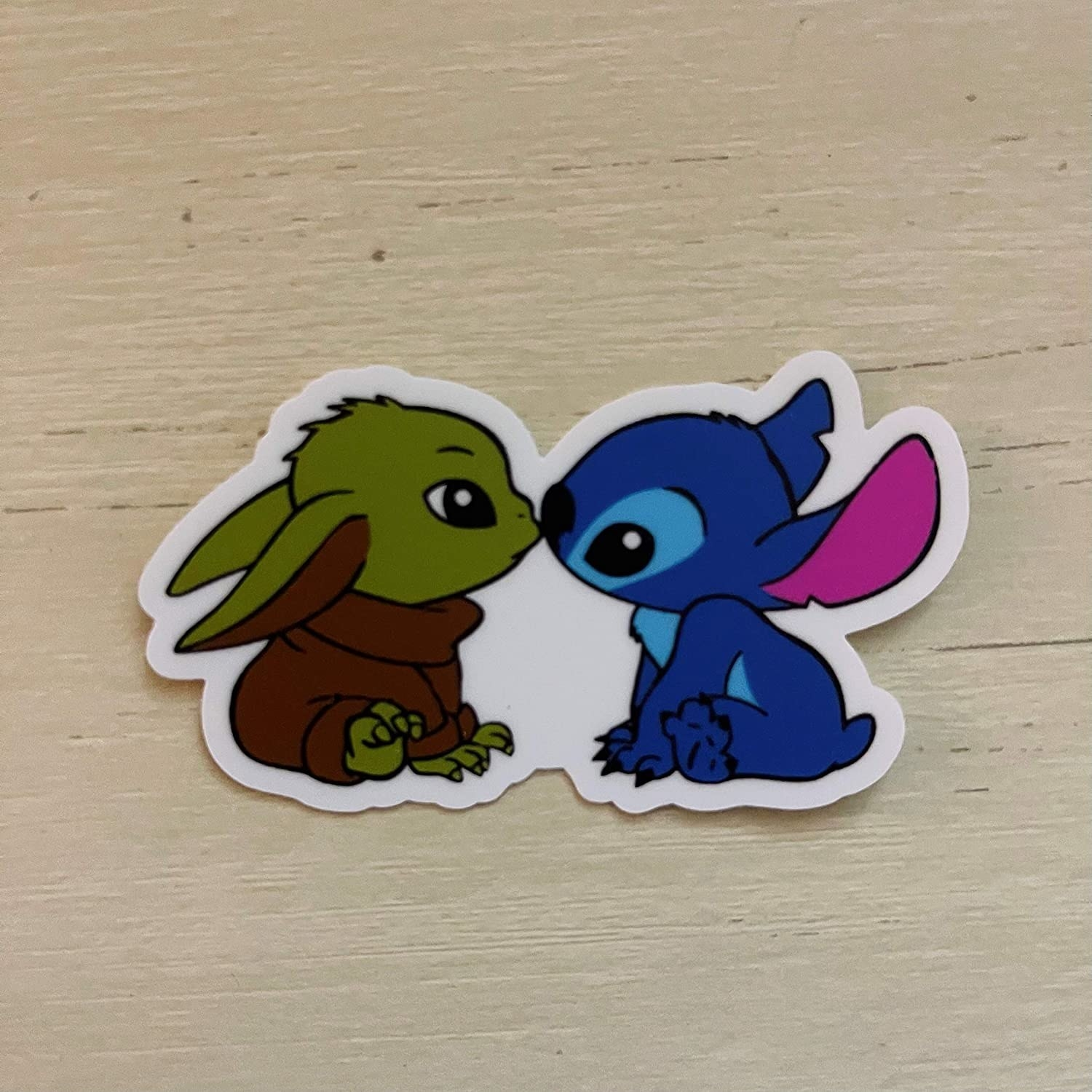 a sticker of baby yoda and stitch touching noses