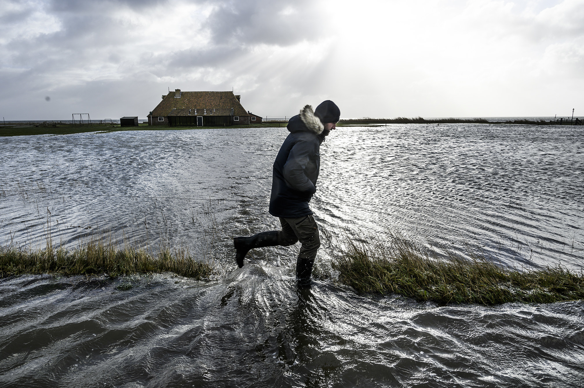 A person walking in deep water with a house off in the distance