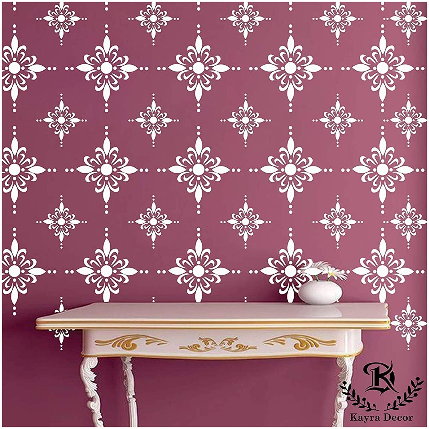 The stencil has a floral design. It's used to create a white floral pattern on a dusty rose coloured wall.