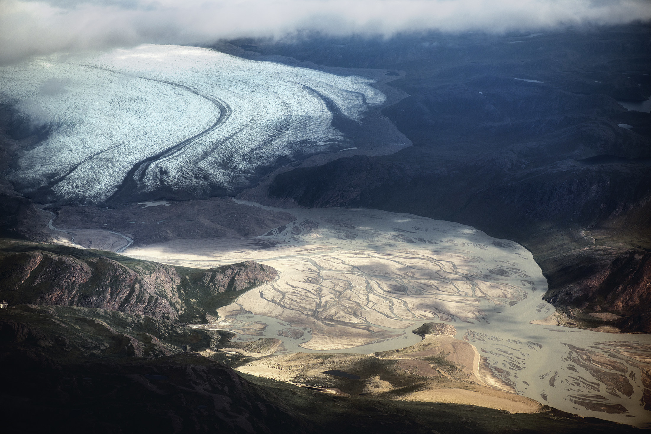 An aerial photo of a large glacier surrounded by mountains that gradually becomes a sandy series of rivers