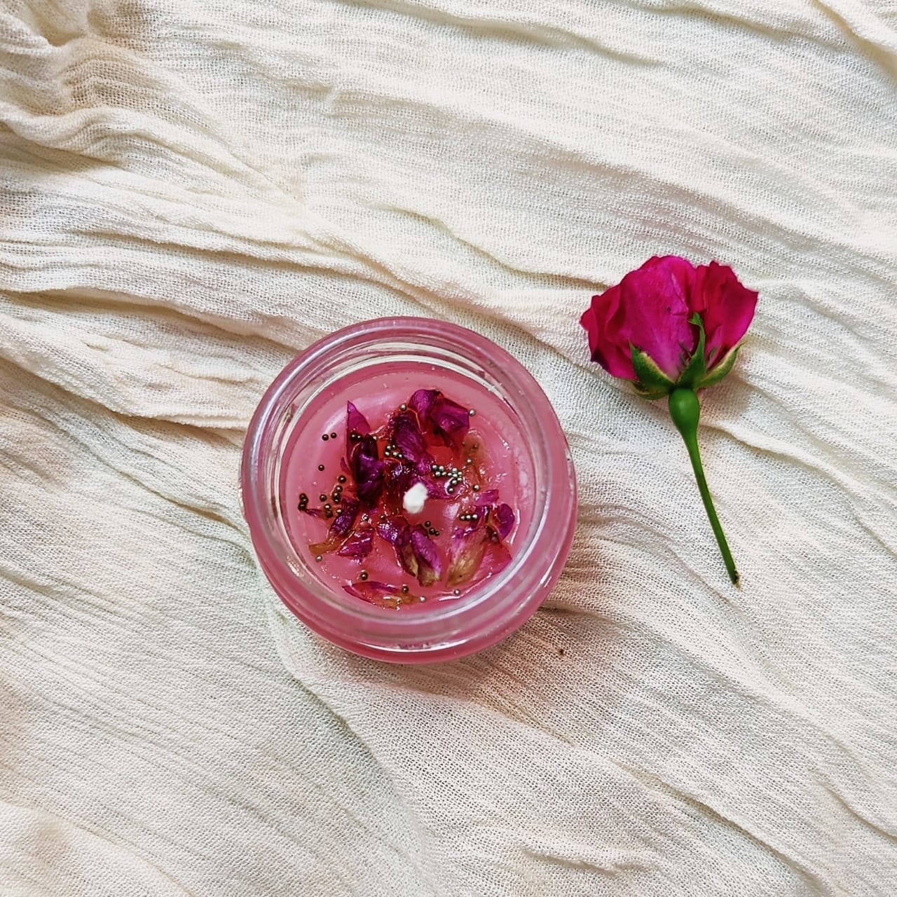A rose-scented candle made in the glass jar. It's kept on white cloth and there's a small rose kept next to it.