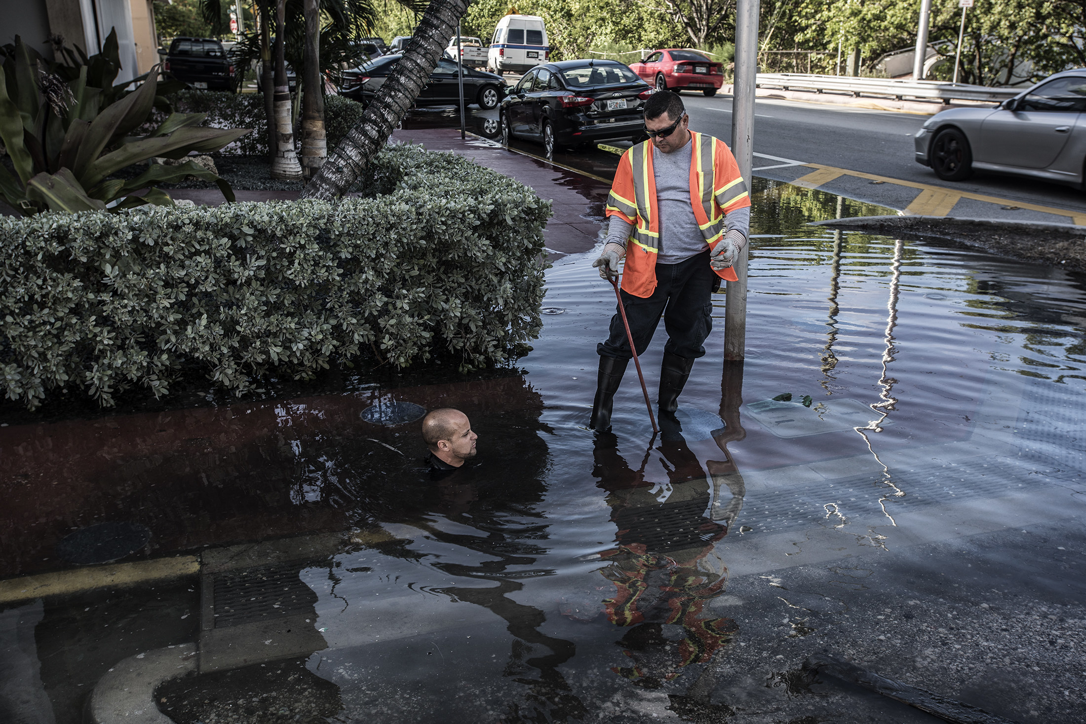 A worker mostly submerged in water with only his head showing on the street, next to another worker standing next to him with water up to his ankles