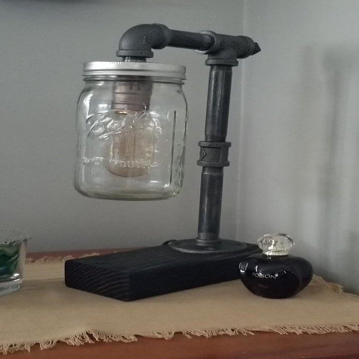 a reviewer photo of the pipe table lamp with a mason jar shade