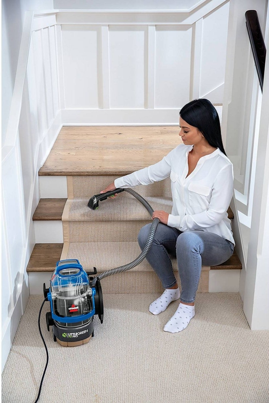 a model uses the bissell little green PetPro to clean carpeted stairs