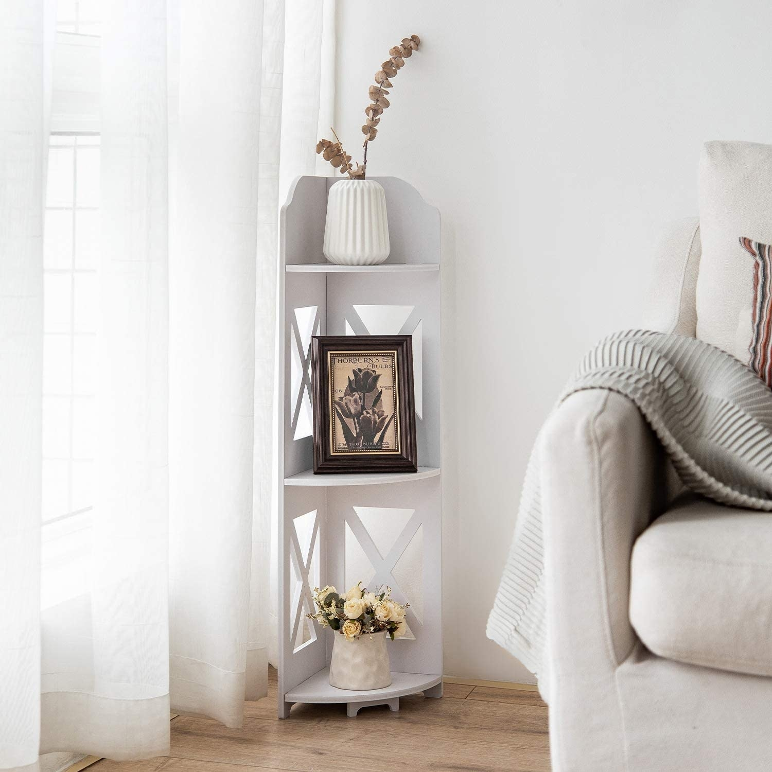 A small white corner shelving unit with three shelves holding plants and frames