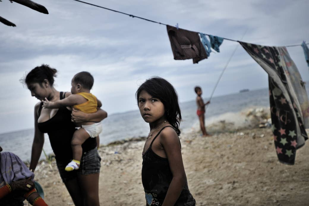 A woman with a few children stands by the sea, with one of the children looking defiant
