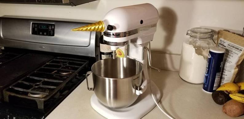 The golden unicorn horn on a white KitchenAid mixer