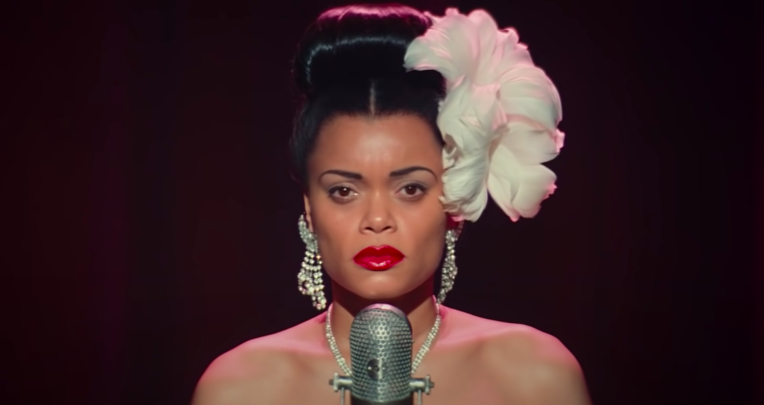 """Andra Day standing in front of a microphone in """"The United States Versus Billie Holiday"""""""