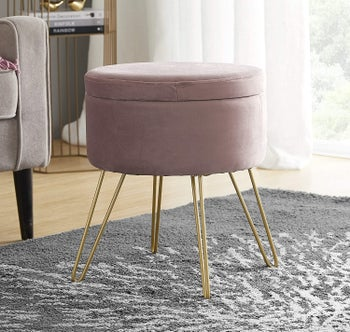 A gold hairpin legged blush pink velvet ottoman with a removable lid