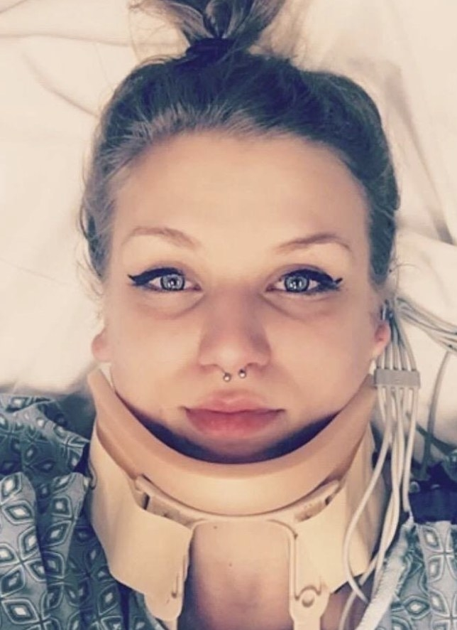 A reviewer photo in a hospital bed wearing aa neck brace and waterproof black eyeliner