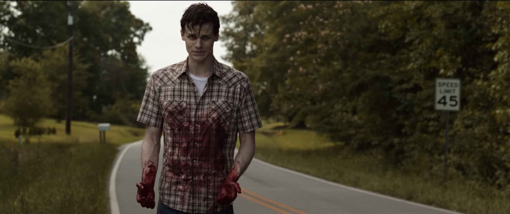 Arne walking down a country road covered in blood