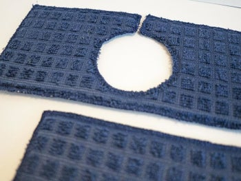 the blue mat with a cutout hole to wrap around faucet head