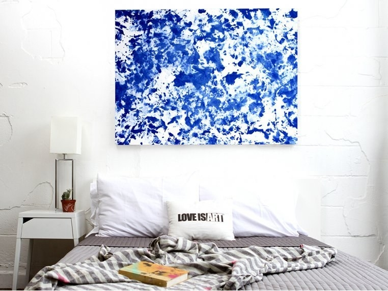 bed with a blue abstract painting hung above it