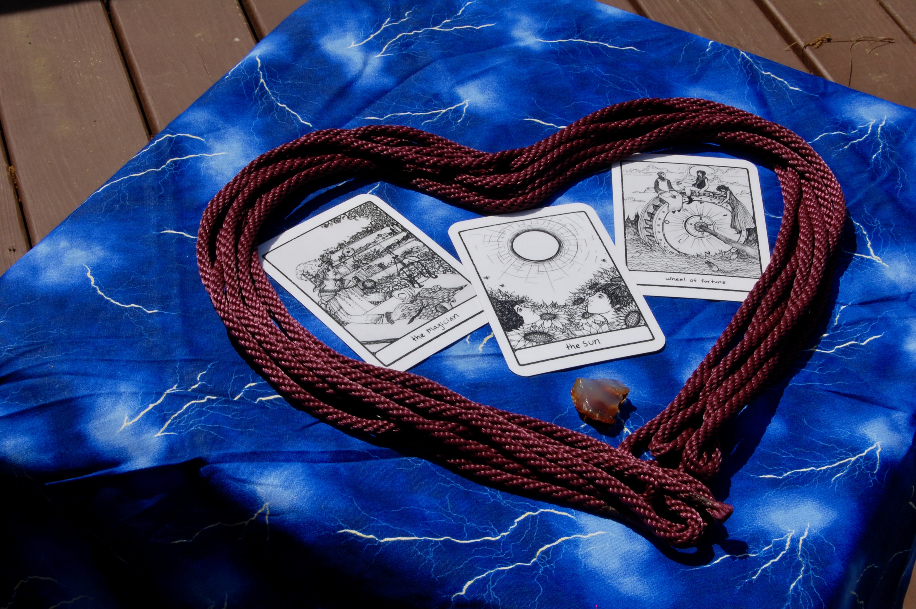 Photo of a rope in a heart shape with three tarot cards (the Magician, the Sun, and Wheel of Fortune), plus a small crystal