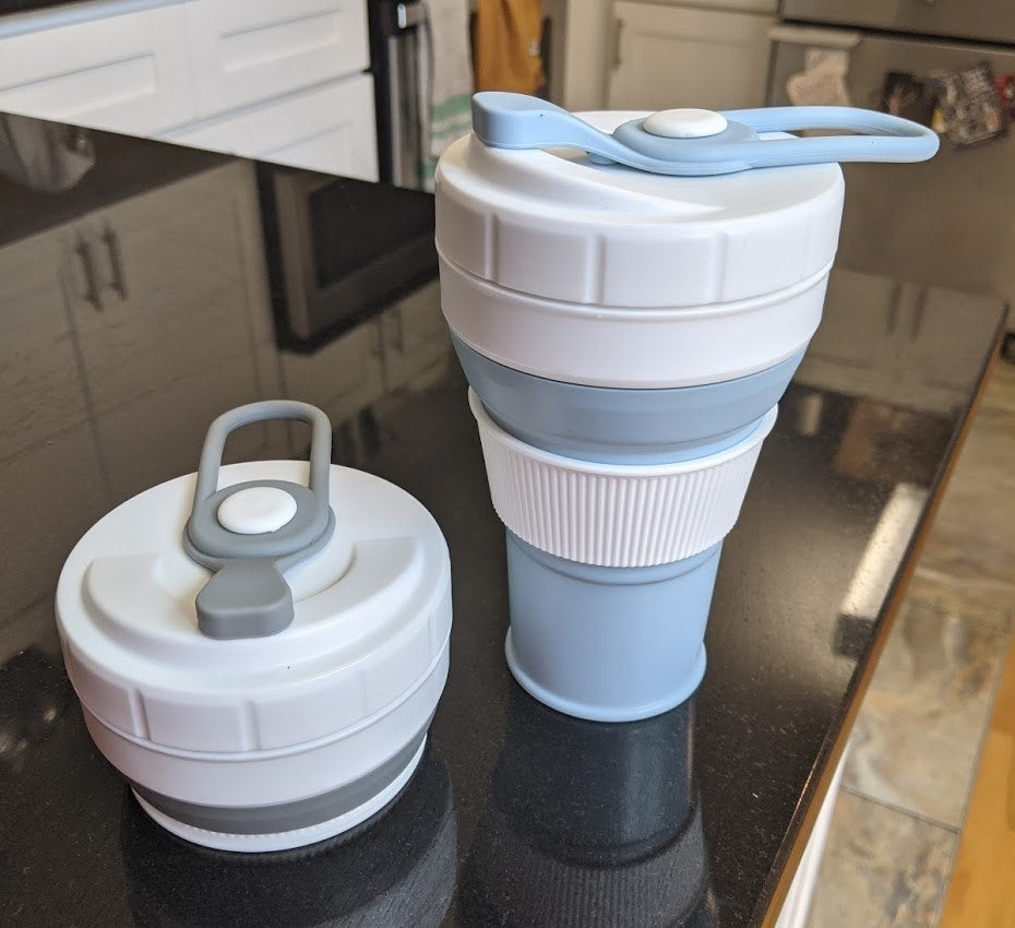A blue coffee cup with a white thermal sleeve sitting next to a gray version of the cup collapsed down into a small disc