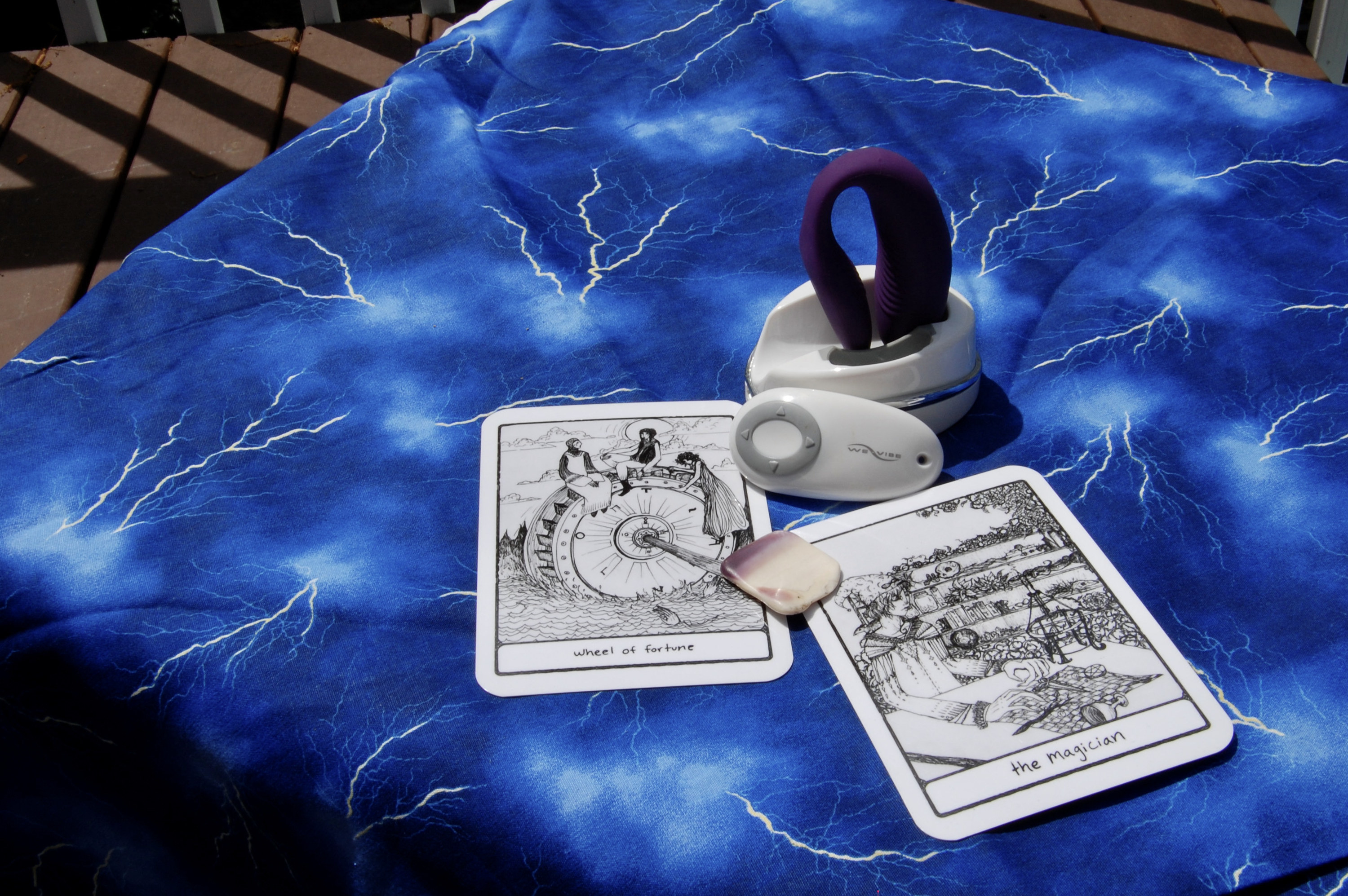Photo of purple We-Vibe Sync with two tarot cards (the Magician and Wheel of Fortune), plus a small, square-shaped shell