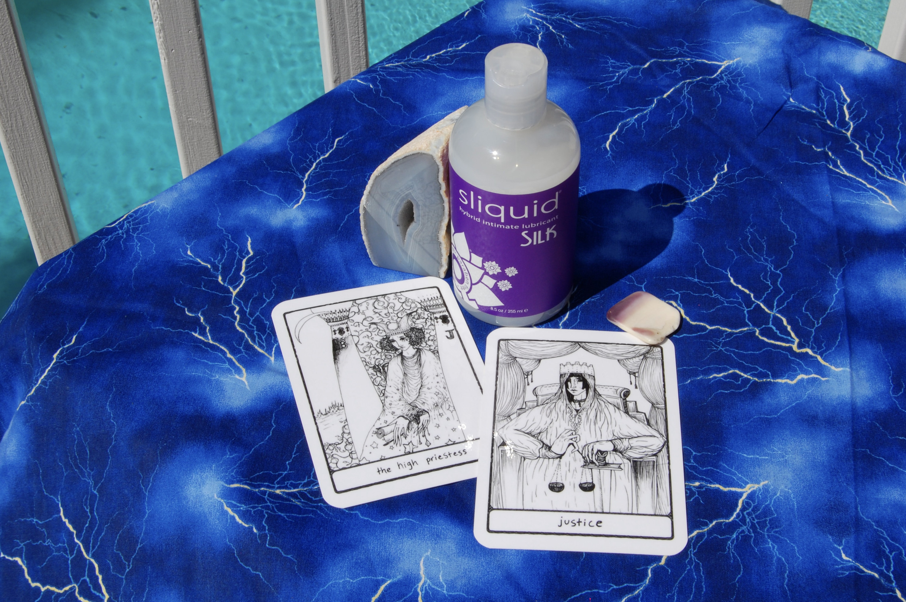 Photo of Sliquid Silk with two tarot cards (The High Priestess and Justice) plus a geode and small, square-shaped shell