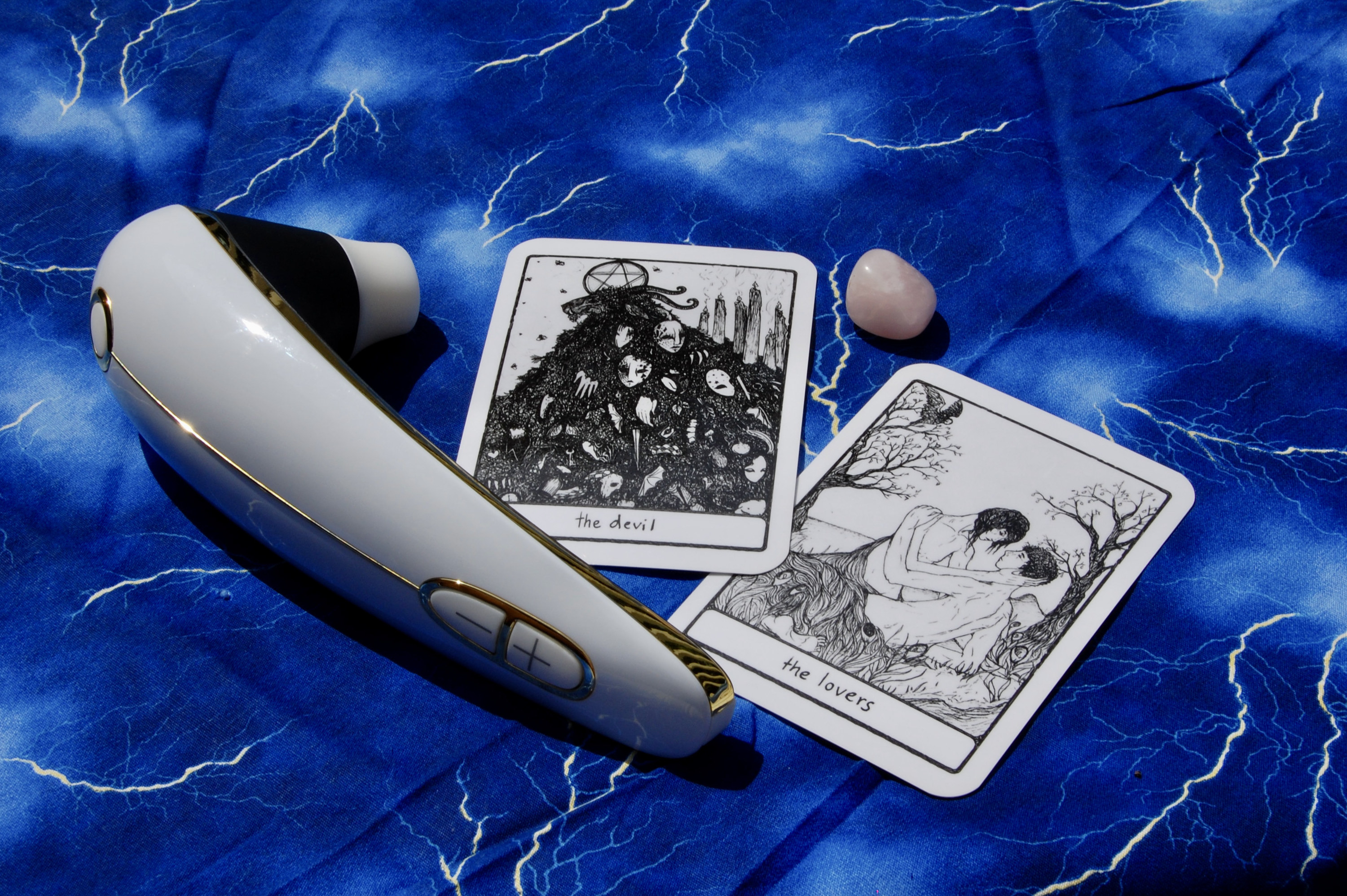 Photo of the Womanizer with two tarot cards (the Devil and the Lovers), plus a small crystal