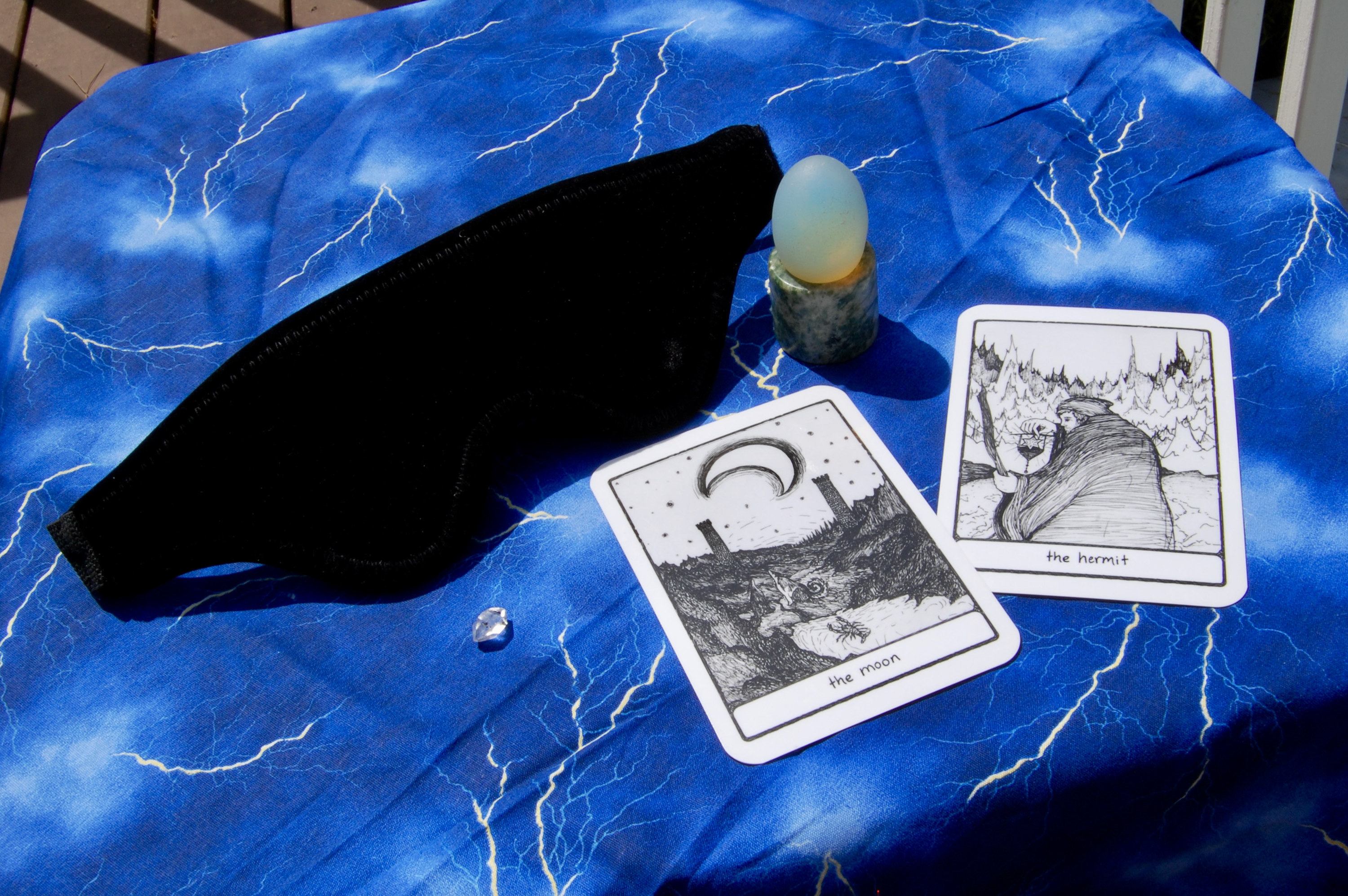 Photo of the Liberator Loveblind with two tarot cards (the Moon and the Hermit), plus a yoni egg and a small crystal