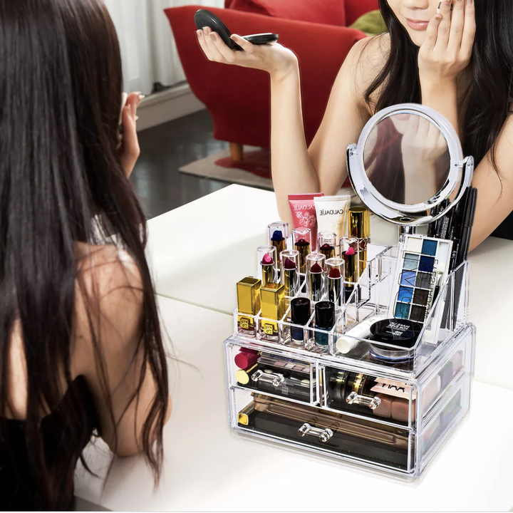 Model sitting at vanity with makeup organizer on top