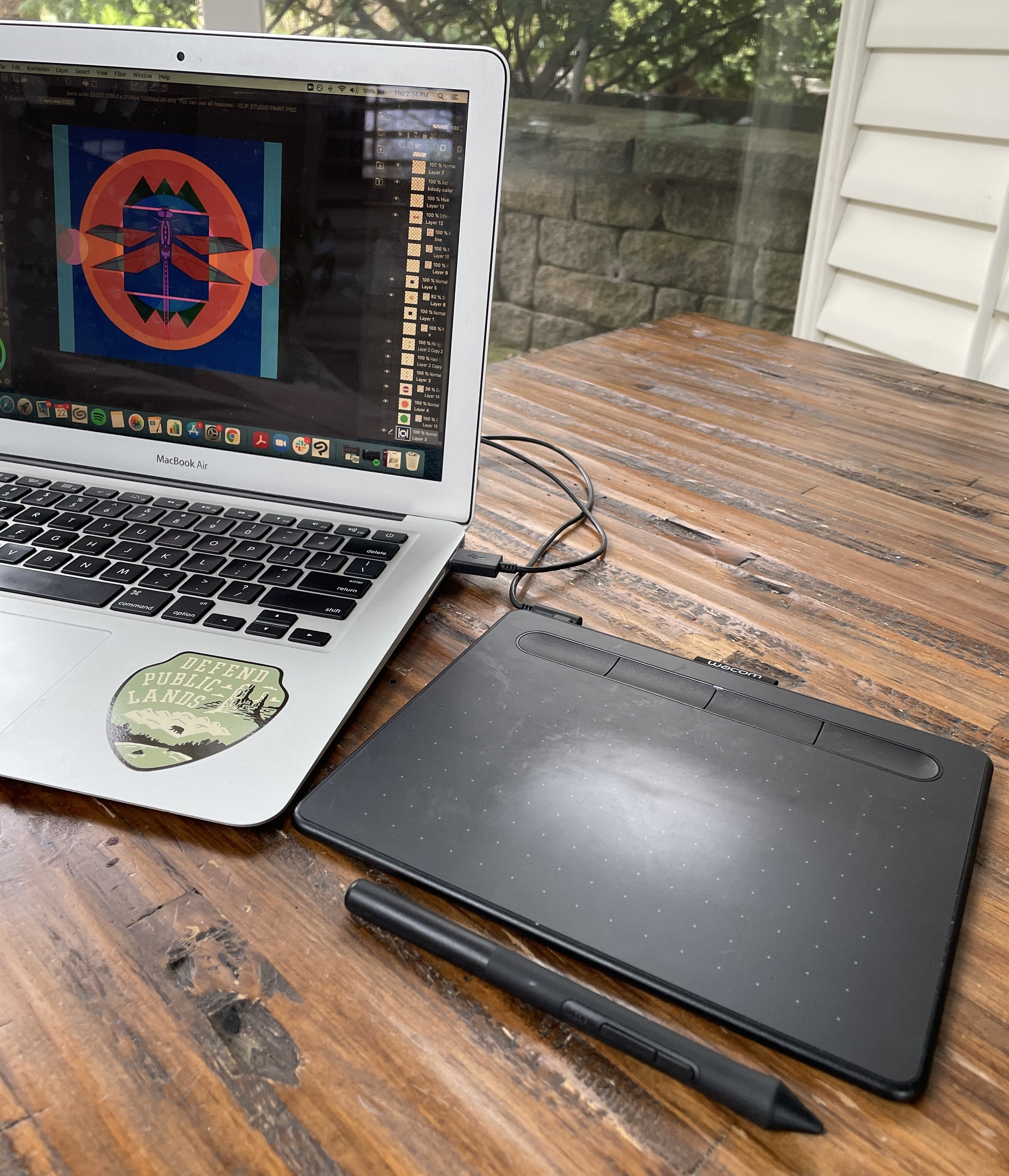 The wacom drawing tablet and stylus plugged into a laptop