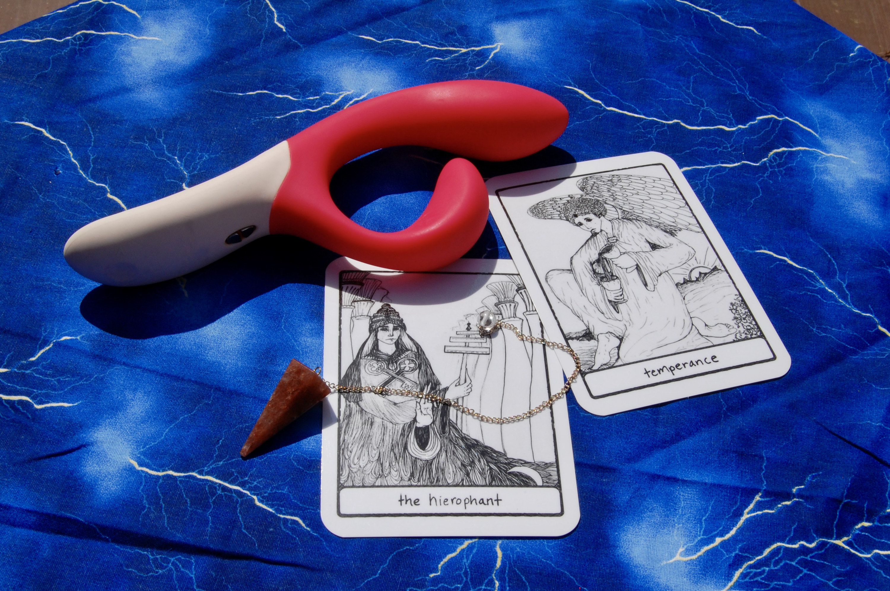 Photo of the We-Vibe Nova with two tarot cards (Temperance and the Hierophant), plus a crystal pendulum