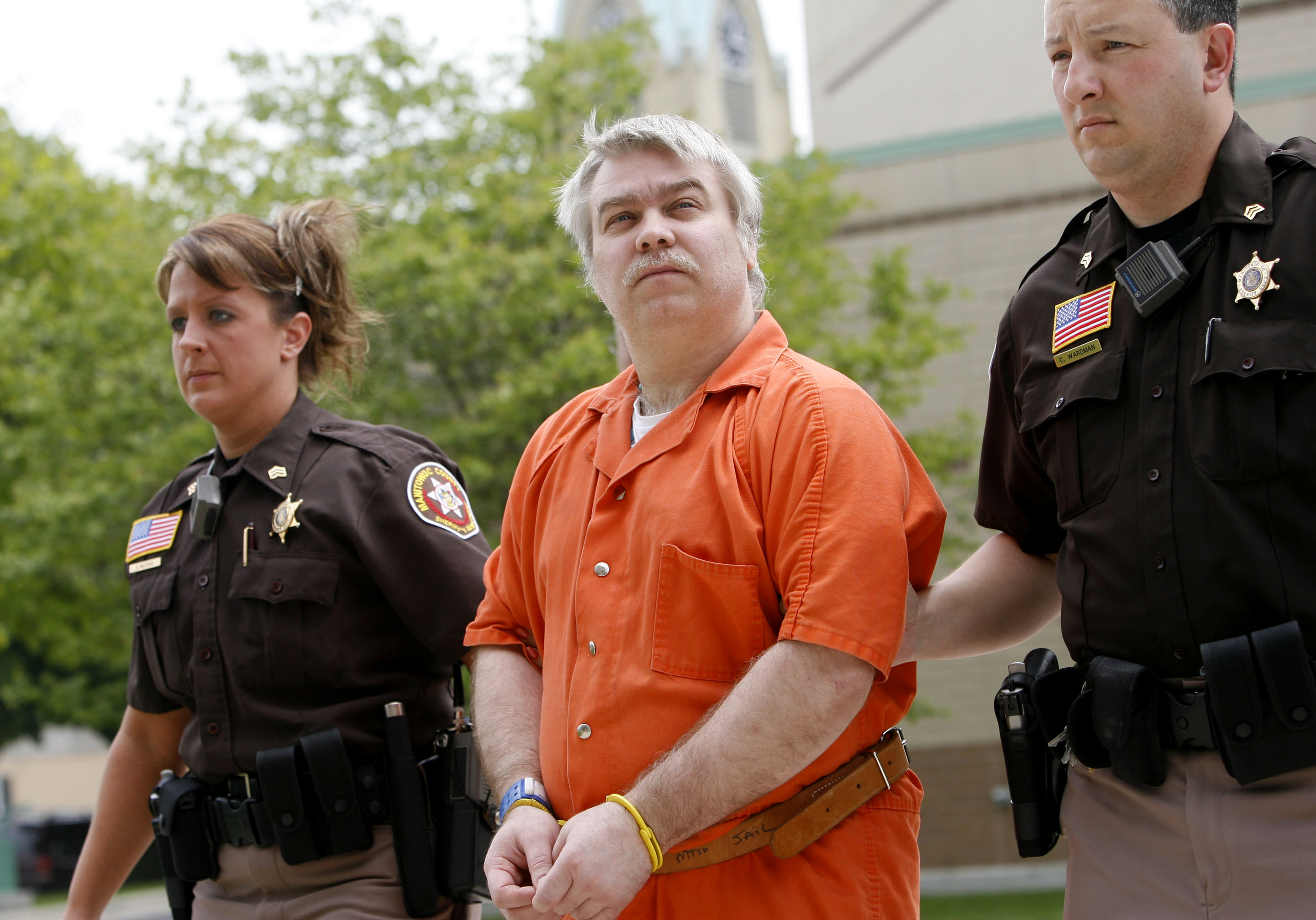 Steven Avery being led away from his home in handcuffs by police