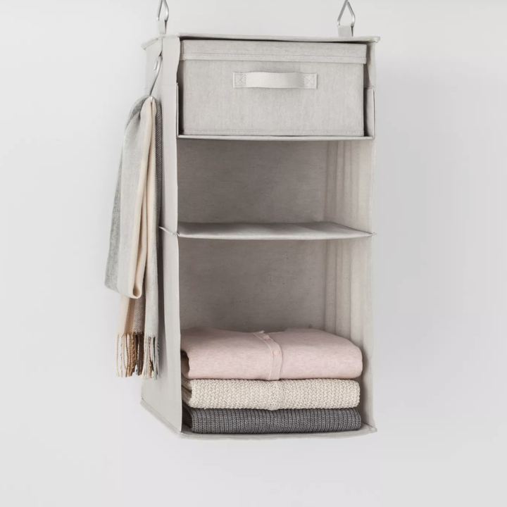 Closet organizer hanging on rod with items placed inside