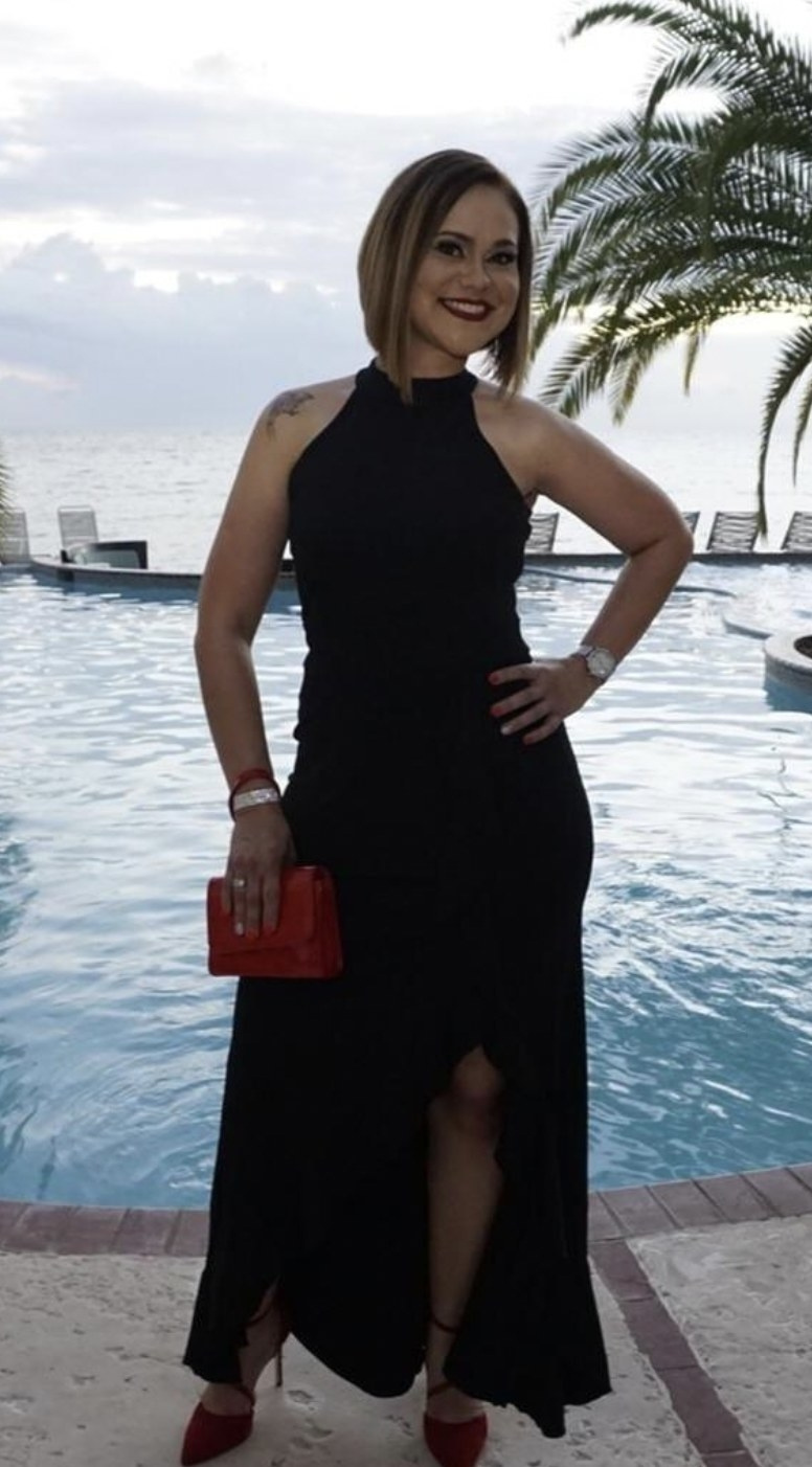 a person wearing a black full length cocktail dress that is sleeveless and has a slit in the skirt