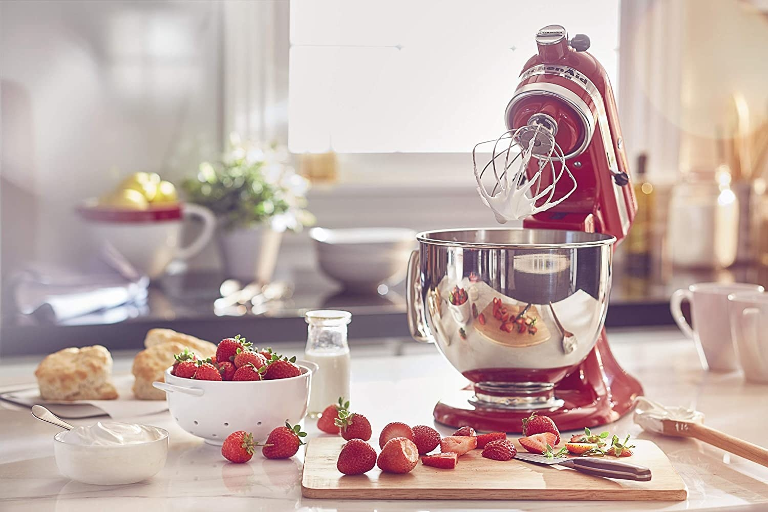 the mixer with some cream on the whisk and surrounded by strawberries