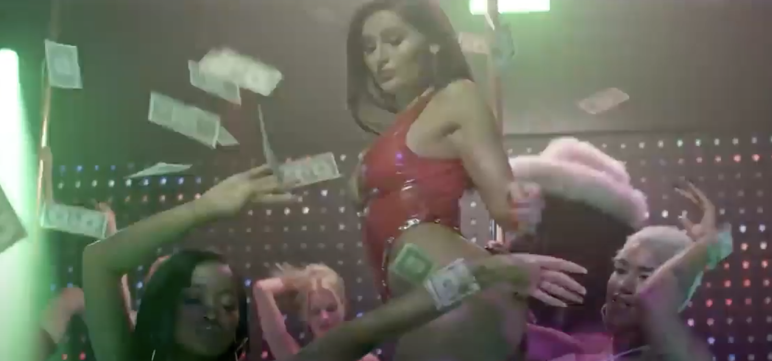 A group of women onstage while money rains down on them