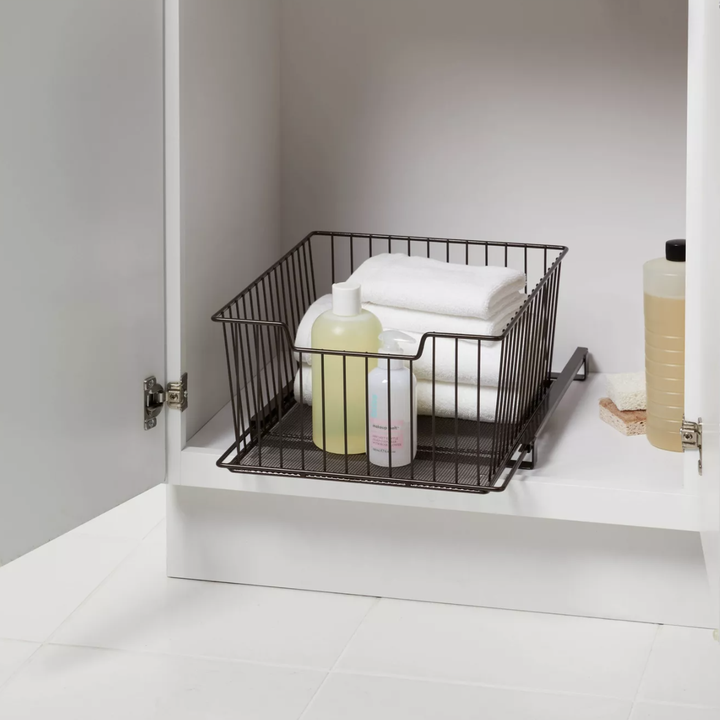 Sliding drawer placed in cabinet with towels and toiletries inside