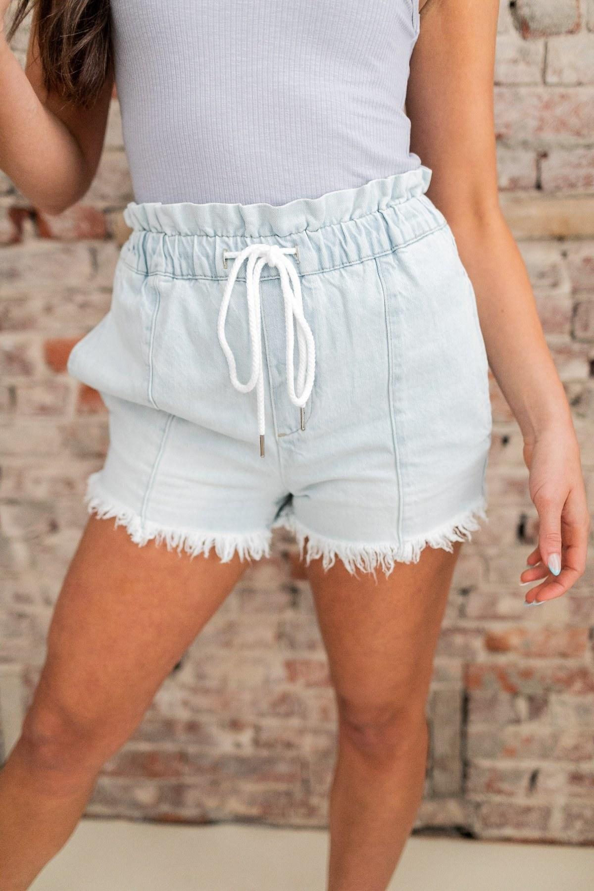 a model wearing the elastic waist fringe denim shorts