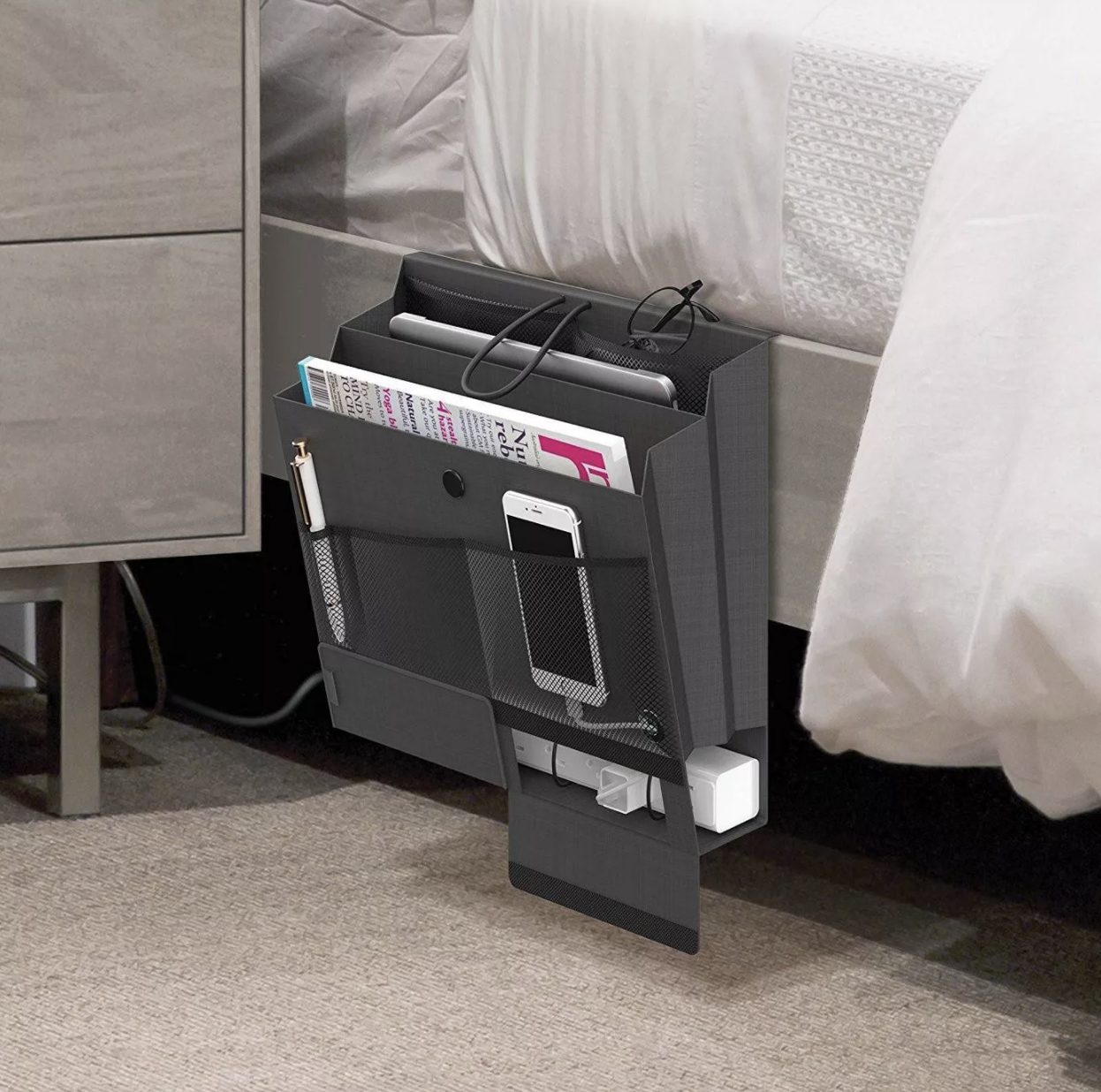 Bedside caddy placed under mattress with various items inside