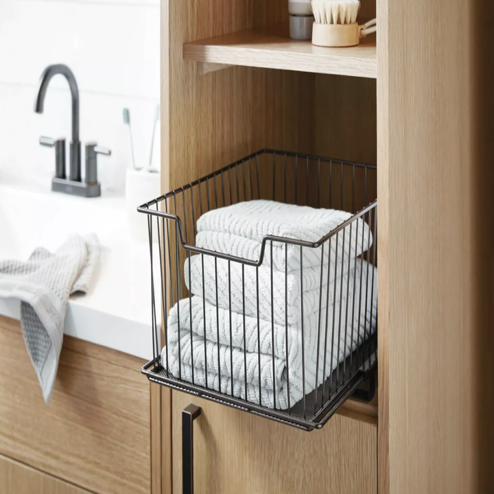 Sliding drawer placed in cabinet with towels inside