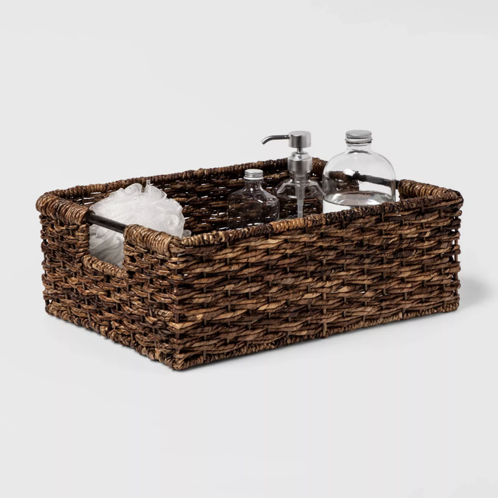 Wicker storage basked with various toiletries placed inside
