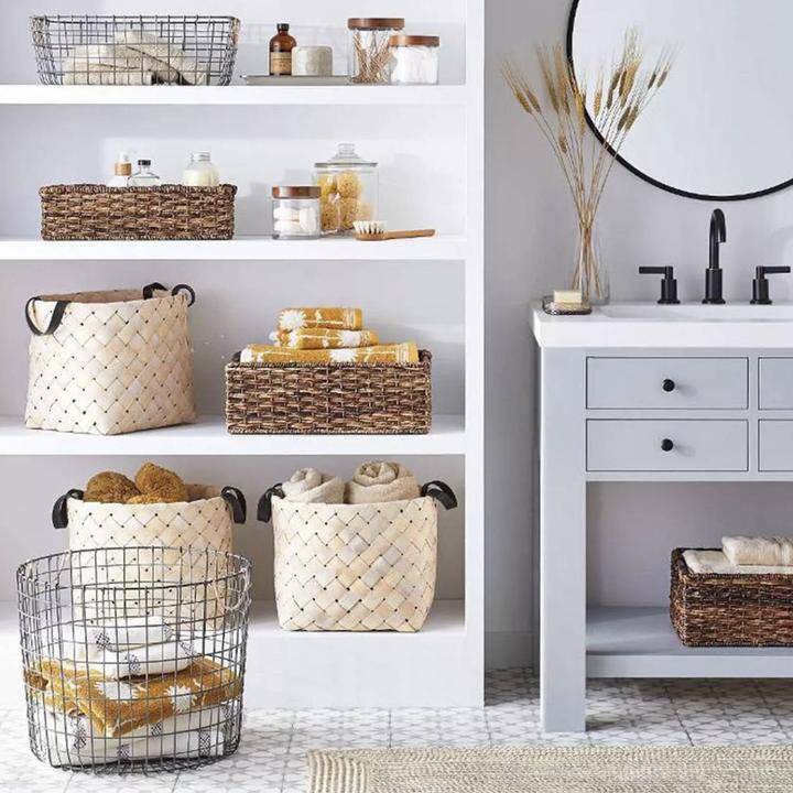 Bathroom shelf with wicker storage baskets placed inside